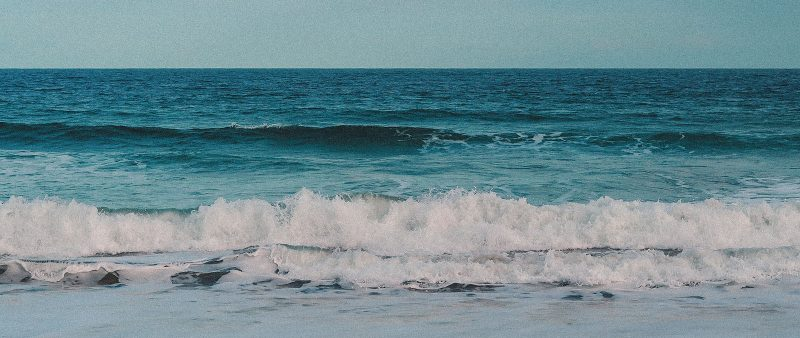 Waves breaking on the sand of Torquay beach.