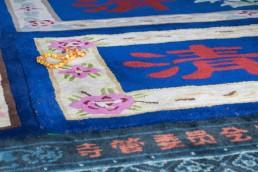 Muslim prayer beads on a blue prayer mat.