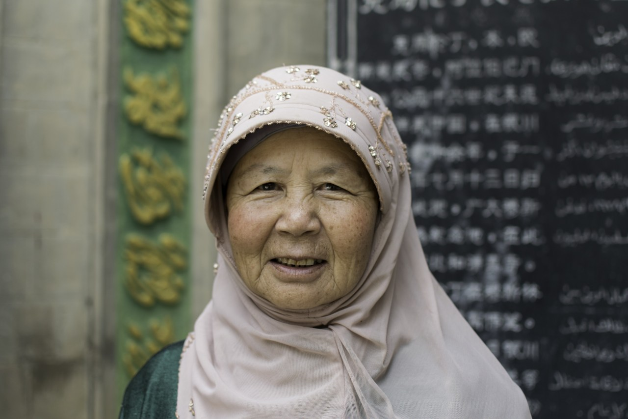 A portrait of a Uyghur woman smiling in a pink hijab.
