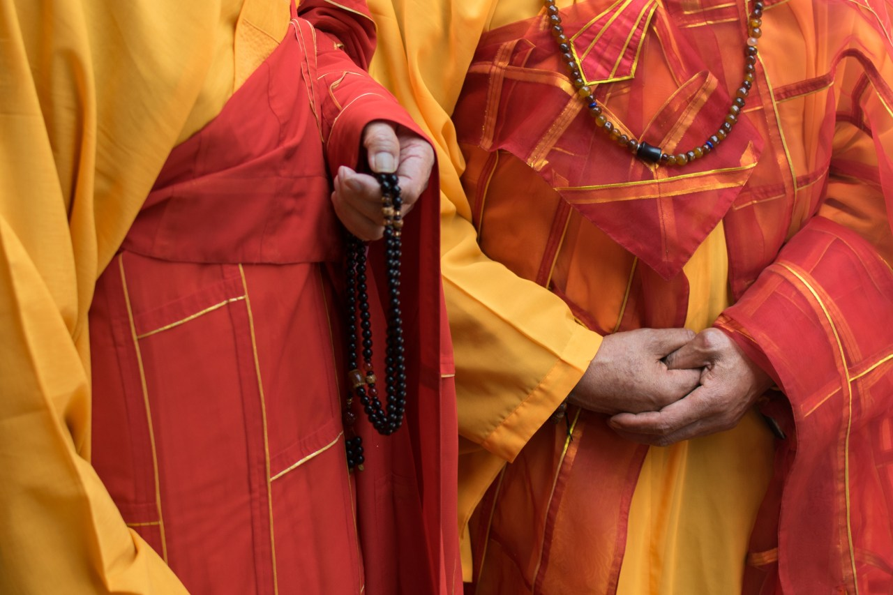 Two monks in traditional garb holding Buddhist prayer beads.