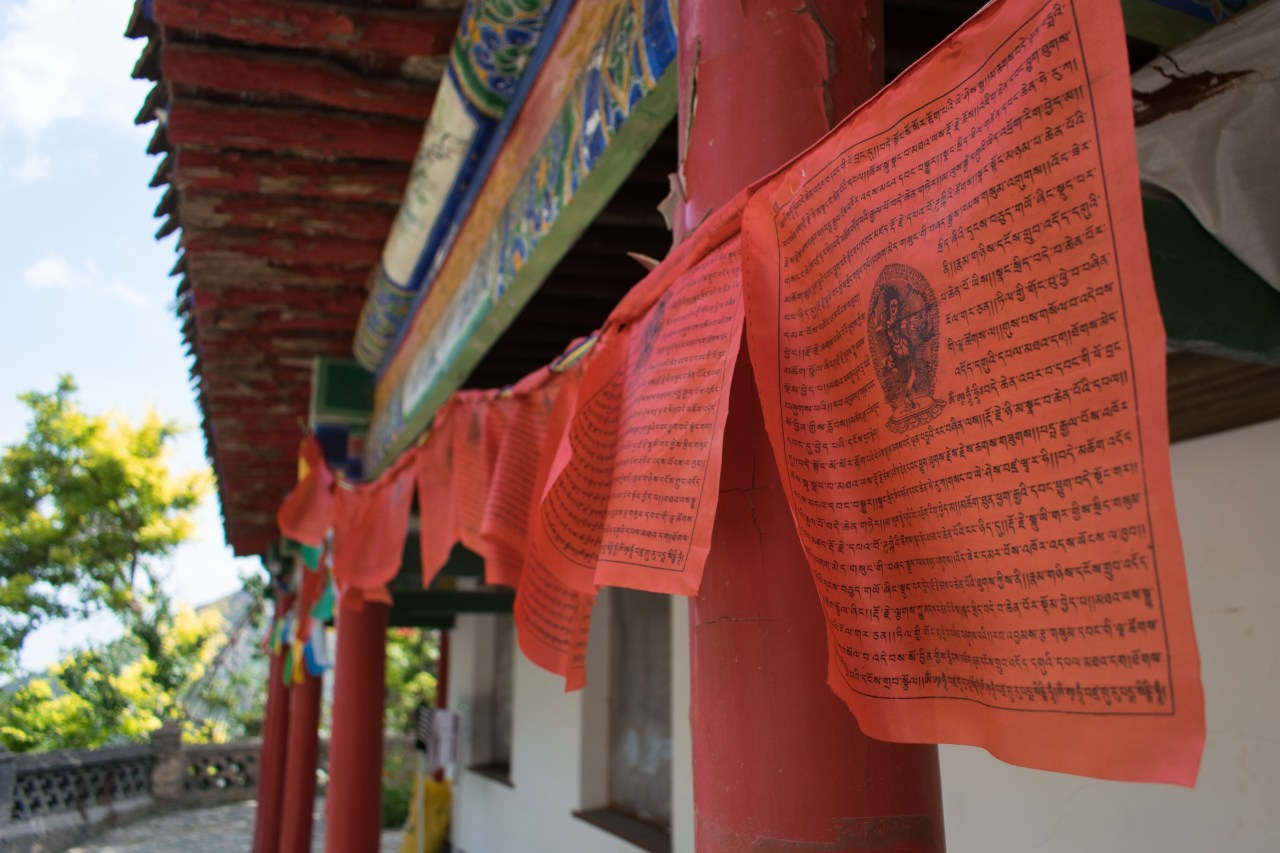 Red prayer flags hanging outside a temple.