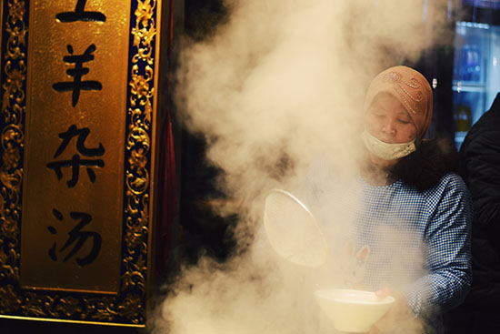 A Chinese Uyghur chef cooking mutton soup in a shop front.