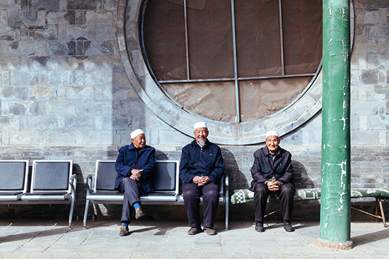 3 Uyghur men sitting on a bench laughing and smiling together.