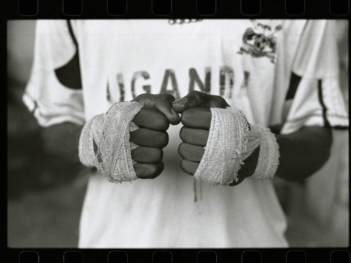 A young, female boxers hands strapped up in white boxing straps.